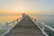 The wooden pier at the sea wiht sunset