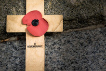 Wooden Memorial Cross With A Red Poppy.