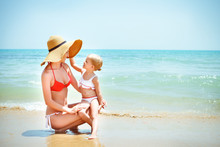 Happy Mother And Her Baby Daughter On Sea Coast