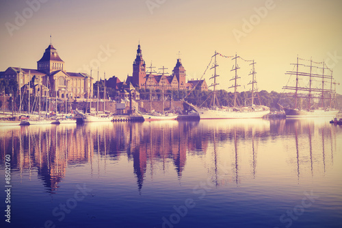 Obraz Vintage style picture of sailing ships in Szczecin at sunrise, Poland. - fototapety do salonu