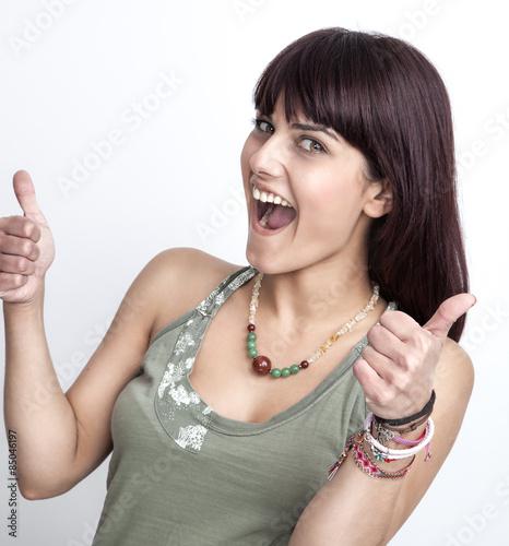 Fotografie, Obraz  Schönes Mädchen freut sich und zeigt beide Daumen nach oben