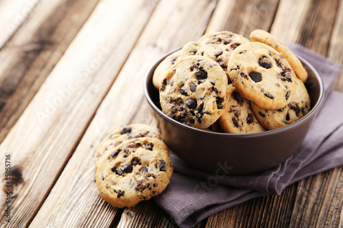 Foto auf Leinwand Kekse Chocolate chip cookies in bowl on brown wooden background