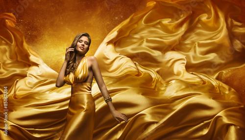Fotografie, Obraz  Fashion Model in Gold Dress, Beauty Woman Posing Flying Cloth