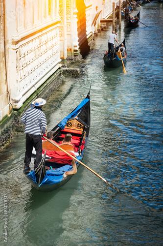 Fotografie, Obraz Venetian gondolier punting gondola through green canal waters of Venice Italy