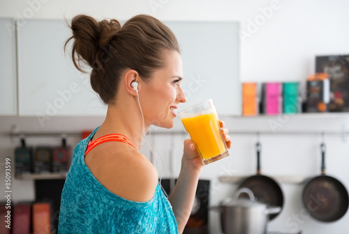 Leinwand Poster Closeup of fit woman in profile starting to drink smoothie