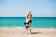 Beautiful woman and her charming daughter resting on the beach