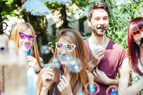 Party! A group of friends, three women and a man have fun at a party in a park with a mustache and fake glasses, joking and talking to each other and playing with soap bubbles in the air!