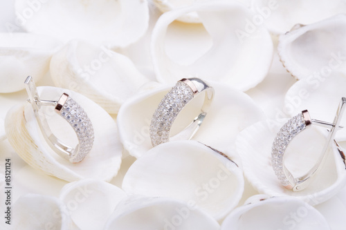 plakat Beautiful gold ring and earrings with diamonds on white seashells.