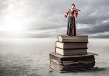 Woman Playing He Violin While Standing On A Pile Of Books