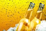 Butelki piwa w kostkach lodu na tle piwa