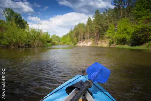 Valokuva  Blue paddles are lying on kayak. Kayaking on a river