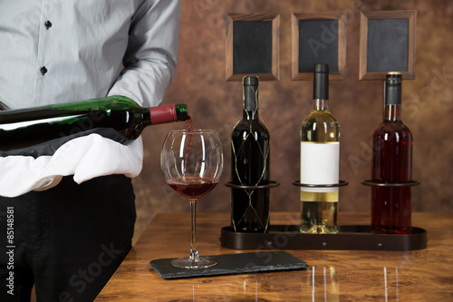Fotografía  Bei einer Weinprobe gießt der Sommelier rotwein in ein Glas