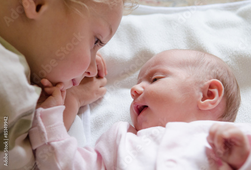 Close up of boy playing with newborn baby