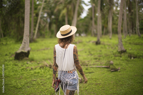 Rear view of a woman walking in a tropical garden, Thailand