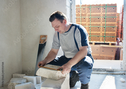 Man measuring a silicate brick with a ruler