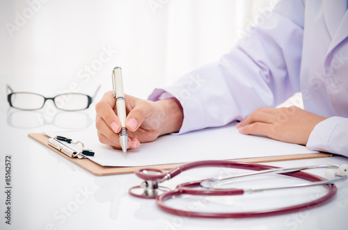 Fotografia  doctor writing record on folder on desk in office