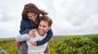 Young guy piggybacking his girlfriend outdoors