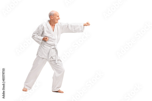 Deurstickers Vechtsport Old man in a white kimono practicing karate