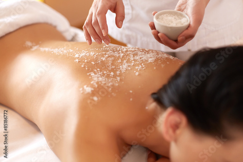 Spa Woman. Brunette Getting a Salt Scrub Beauty Treatment in Salon