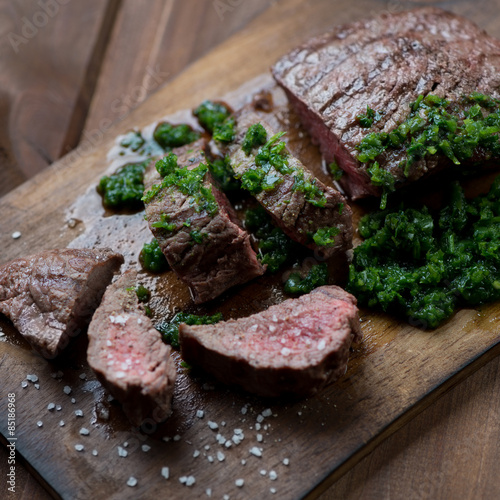 Medium rare grilled beef steak with chimichurri, selective focus Poster