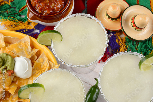 Fotografie, Obraz  Margaritas: High angle view of three margarita cocktails surrounded by nachos, chips and salsa on a bright Mexican, table cloth