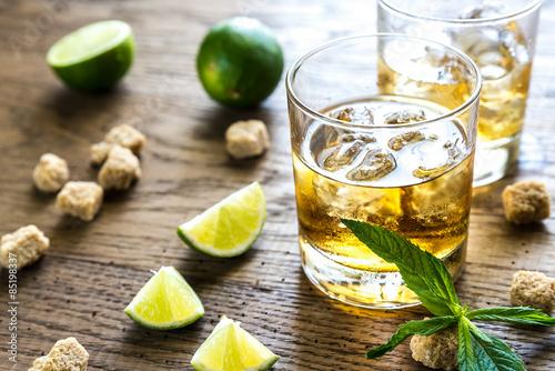 Glasses of rum on the wooden background Fototapeta