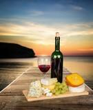 Winogrona, ser i wino na tle zachodzącego słońca