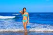 Brunette happy girl walking in the beach shore