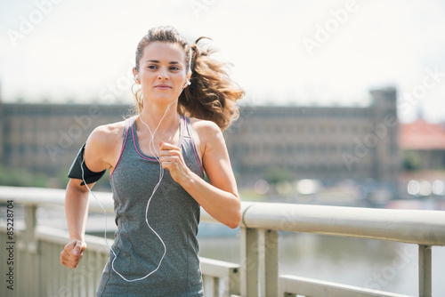 Valokuva Smiling woman jogging in urban setting listening to music