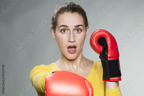 Fotografie, Obraz  surprised young woman punching with boxing gloves for self-defense concept