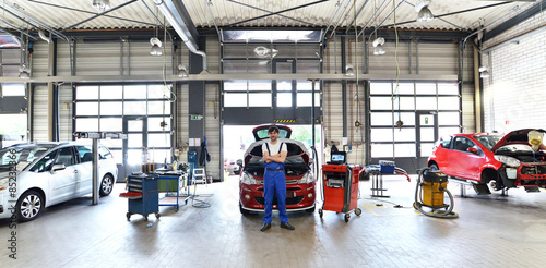 Photo  car mechanic in a garage with vehicles // moderne Autowerkstatt