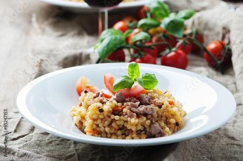 Photo  Cooked sardinain pasta fregola with tomato and sausage