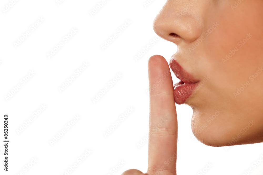 Fototapeta finger on her lips. silence gesture