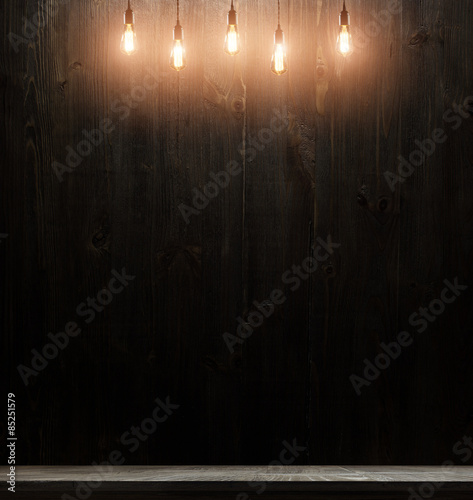 Fotografia wooden interior room with classic Edison light bulb on wooden background switched on