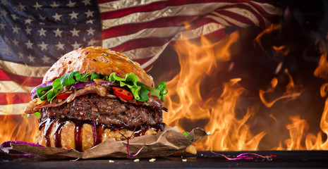 Panel Szklany Do steakhouse Delicious hamburger with fire flames