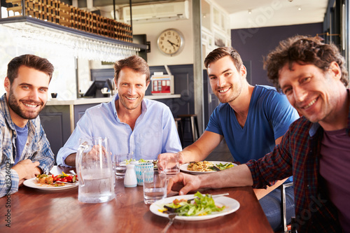 Foto op Canvas Kruidenierswinkel A group of men having lunch in a restaurant