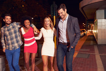 Four Friends Walking Through Town Together At Night