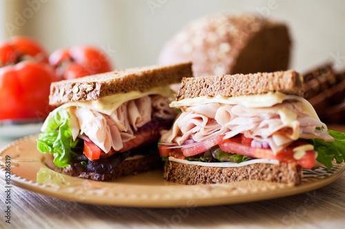 Deli Sandwich - Sliced Roast Turkey, whole grain brea, sliced tomatoes, crisp lettuce, and cheese.