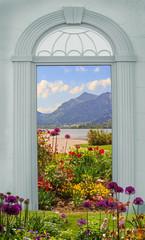 Fototapeta Do salonu blauer Torbogen mit Blick auf Blumenbeet, Schliersee und Brecher