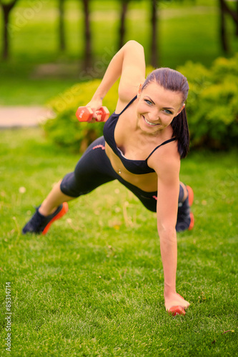 Fotografie, Obraz  Female fitness instructor exercising with small weights in green