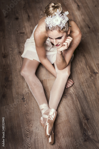 Female ballet dancer sitting on ground Plakát