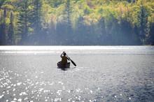 Boy Paddling A Canoe Across A Lake