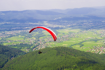 FototapetaParaglider over village in mountain