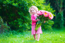 Little Girl With Peony Flowers In The Garden