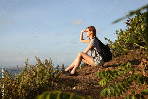 Poster Marron chocolat Girl sitting at the edge of rock and looking at the horizon