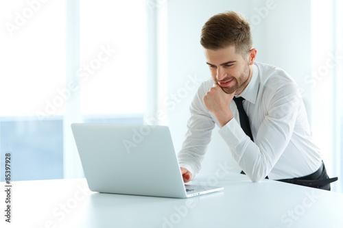 Fotografía  El hombre de negocios hermoso que trabaja en la computadora portátil en su ofici