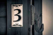 Old Apartment Number Sign On The Wall Of Wood With The Number Three On It. Sepia Colors.