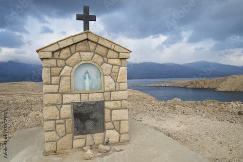 Fotografie, Obraz  Marienfigur auf der Insel Pag mit dramatischem Himmel vor dem Velebit Gebirge