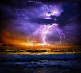 Obraz na Szklelightning and storm on sea to the sunset - bad weather