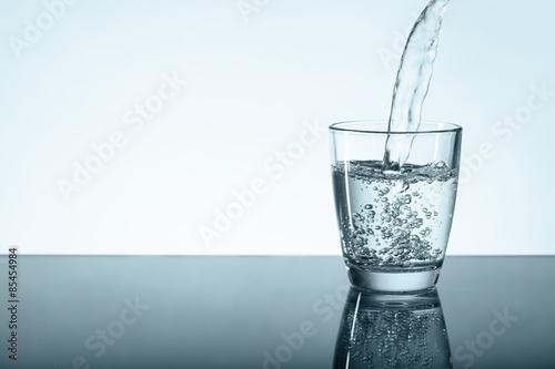Valokuva  Glas auf Tischplatte wird mit Wasser gefüllt